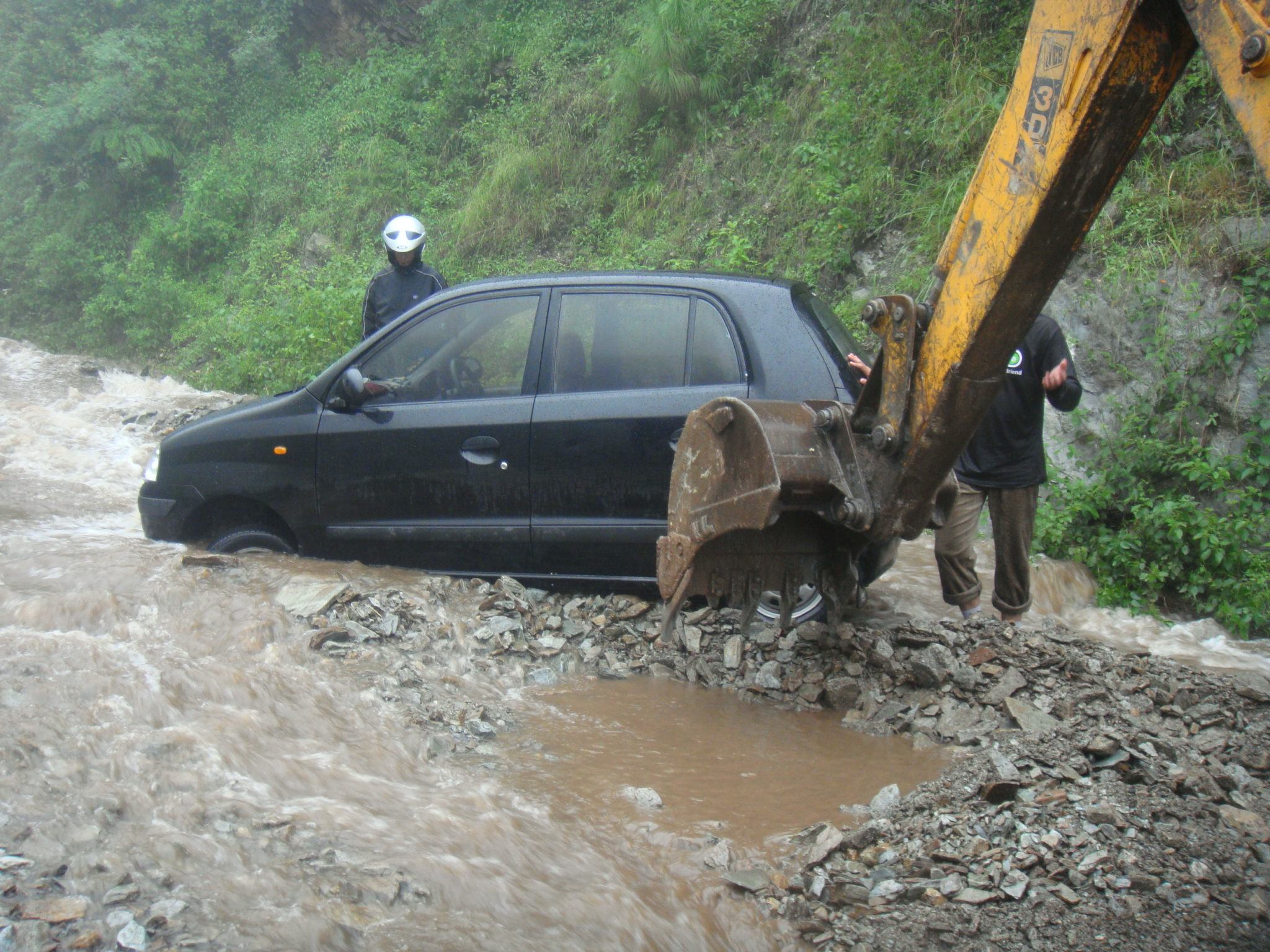the car stuck in a flowing stream; bulldozer to the rescue