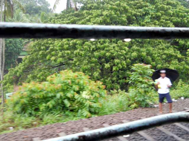 School going boy waits for the train to pass in rain-Kerala