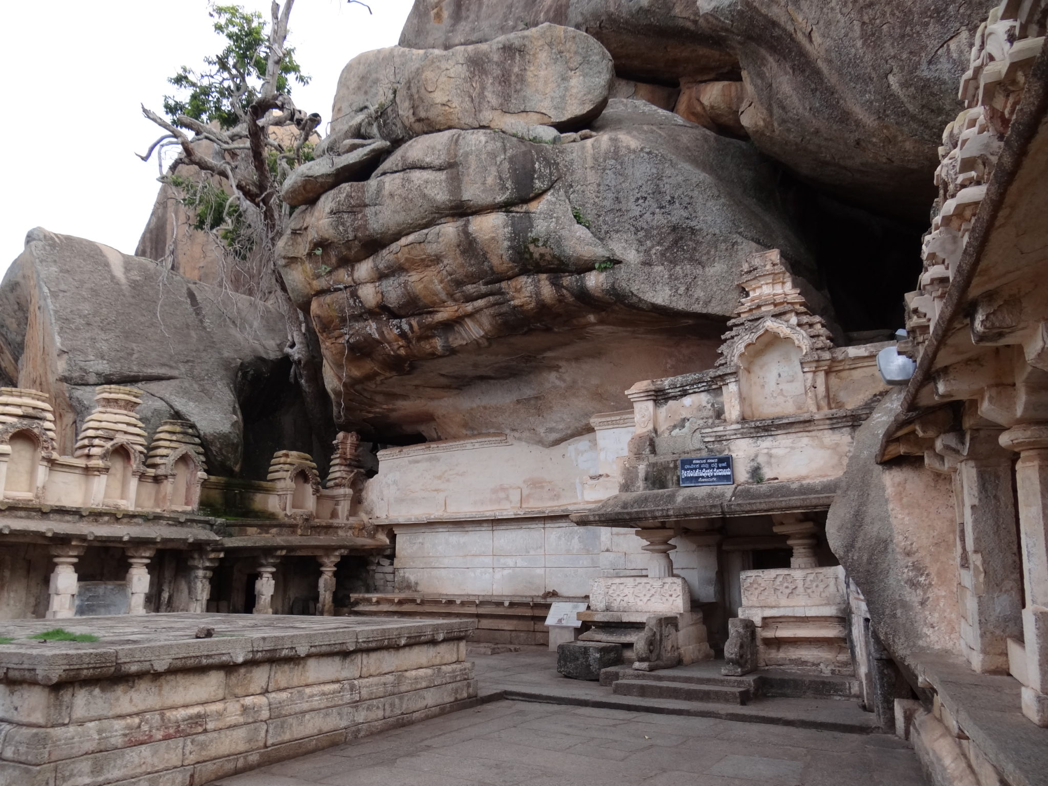 Rock carved temple under the benevolent shadow of boulders