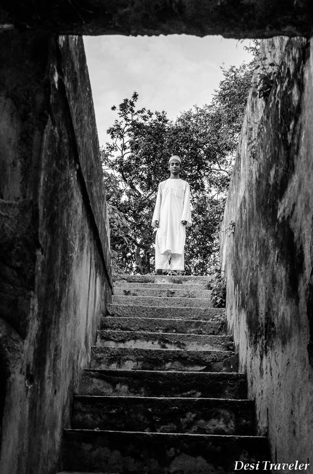 A boy standing on the top of the stairs to the ancient well