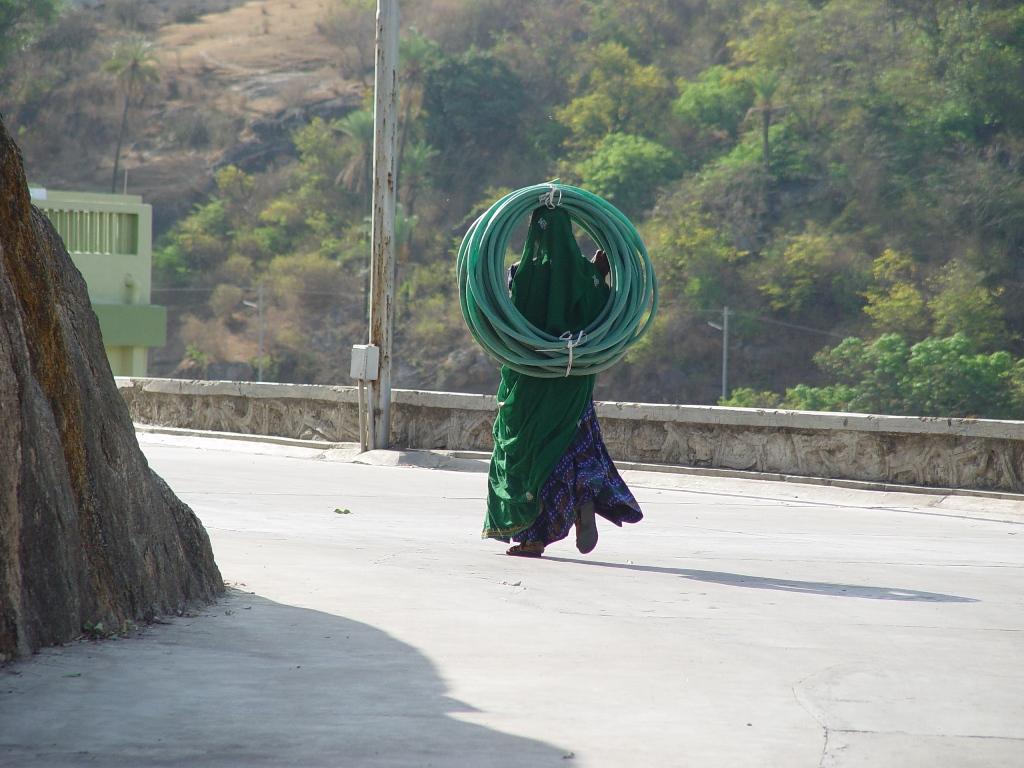 पानी का पाइप सर पर लटकाये जा रही एक राजस्थानी महिला जो यहां माली का कार्य करती होगी!