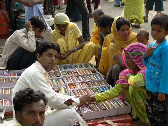 Choori wala (bangle vendor) trying bangles on a villager's hands.