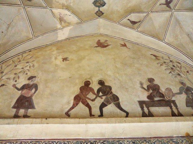 दूसरी मंजिल पर बने हुए कक्षों में किये गए भित्ति चित्र में बादशाह अकबर कुश्ती का मज़ा लेता दिखाई दे रहा है।