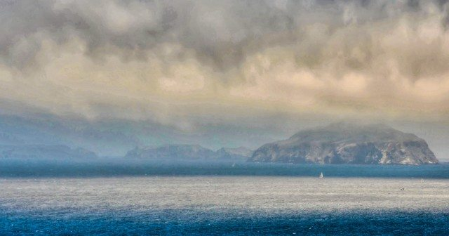 View of the Anacapa Island shrouded by clouds. You can see the reflection of the clouds in water.