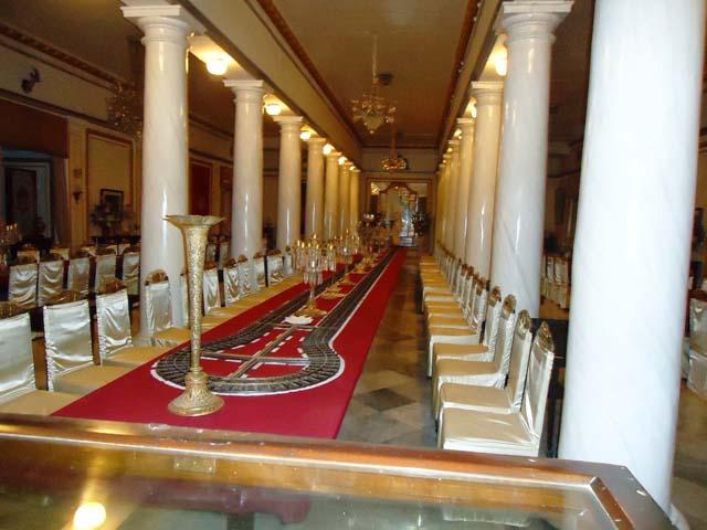 महल का भव्य डाईनिंग हॉल में डाईनिंग टेबल पर चाँदी की ट्रेन से खाना परोसने की व्यवस्था
