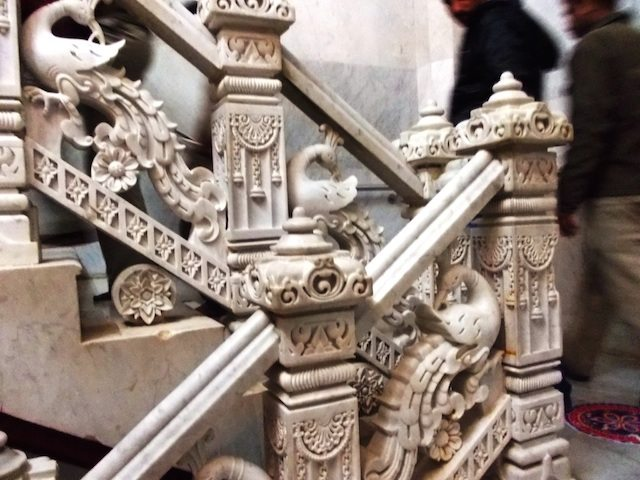 Artistically carved marble pillars along the staircases, engraved with beautifully peacocks