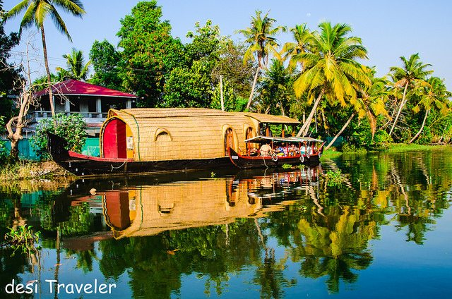 A Luxury houseboat  with a small boat in backwaters of Alleppey