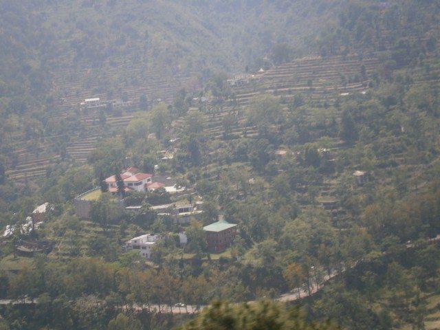 ट्रैन से दिखाई देता एक पहाड़ी गांव तथा साथ साथ चलती सड़क