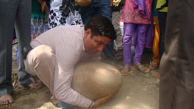 Trying to lift the stone which Maharana Pratap lifted for Puja Offering