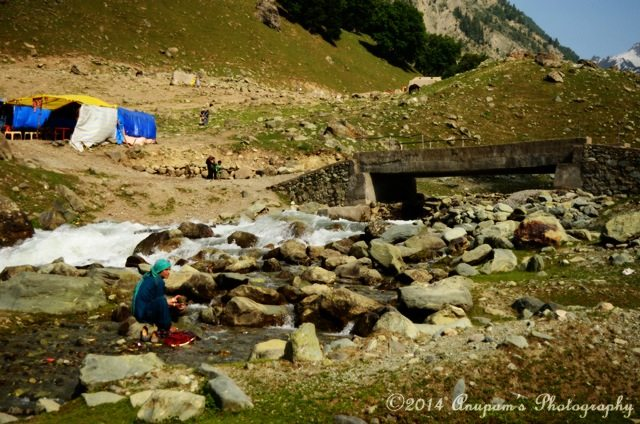 A Lady busy in washing clothes on the stream