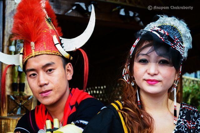 A Naga couple sitting in front of their Morung