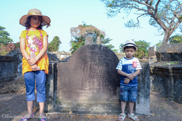 My kids in front of a tombstone