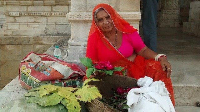 मंदिर के बाहर पुष्प बेचती महिला