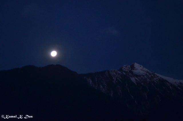 Moon looming large over mountain peak.